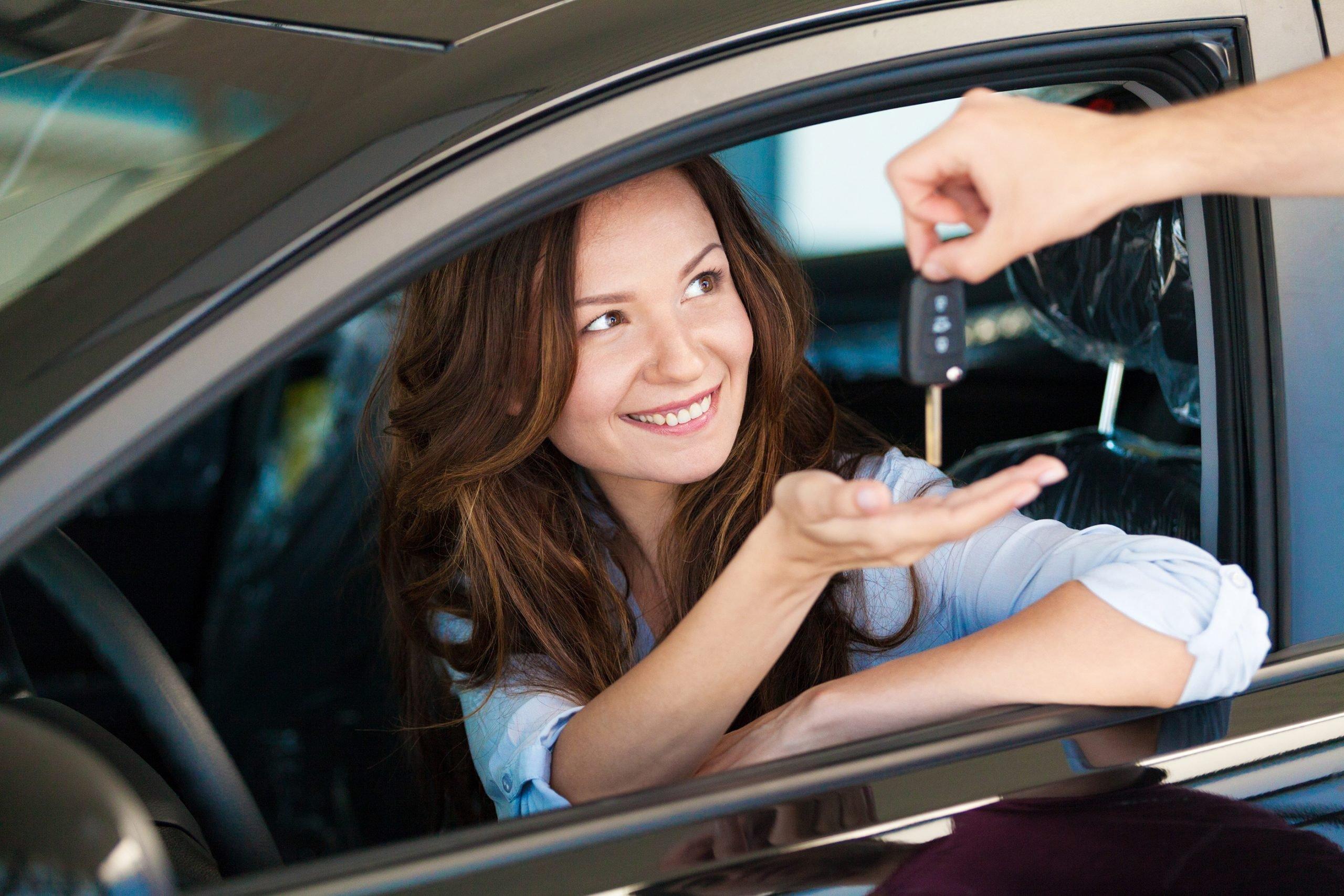 woman in car reaching for keys