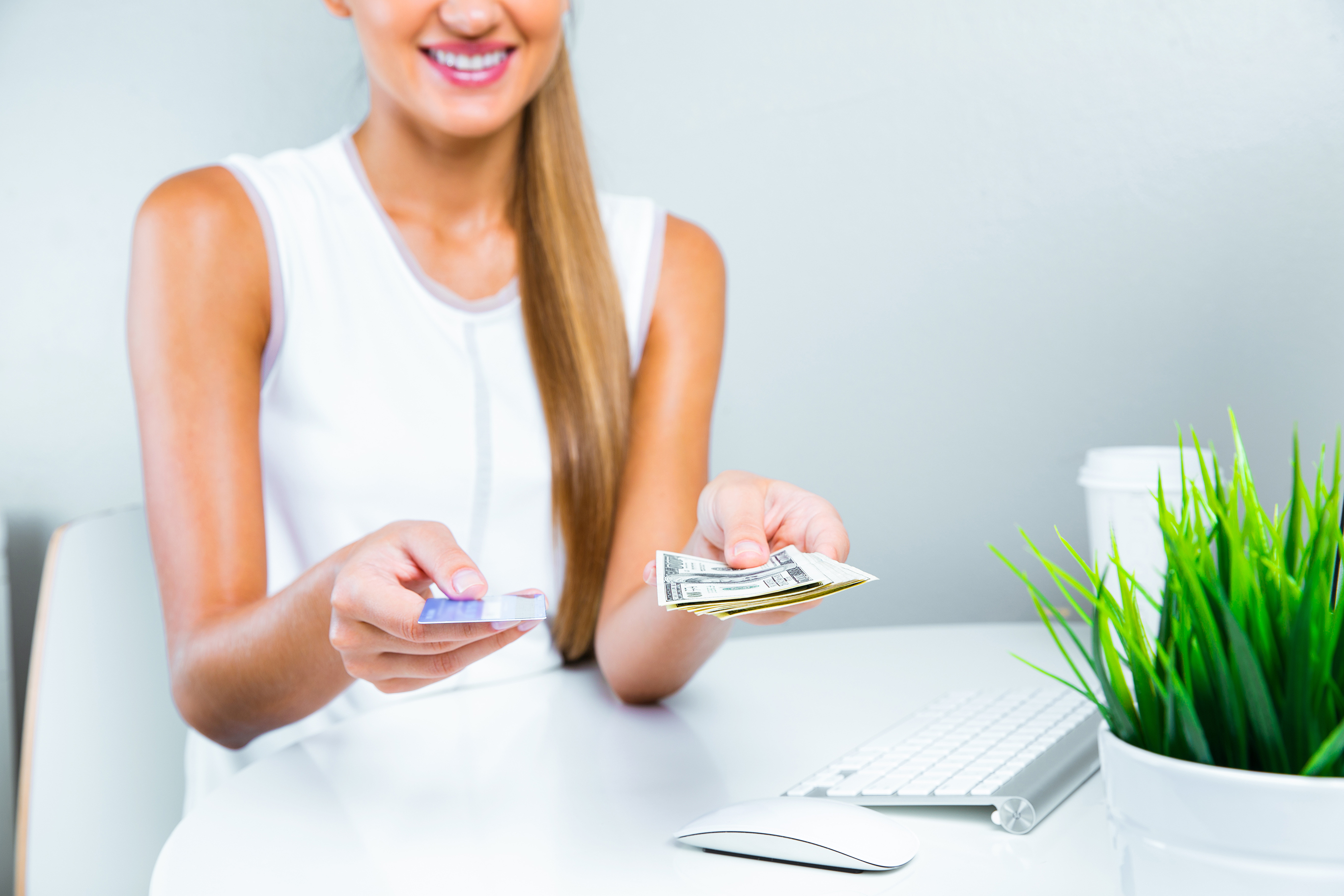 woman holding cash and card