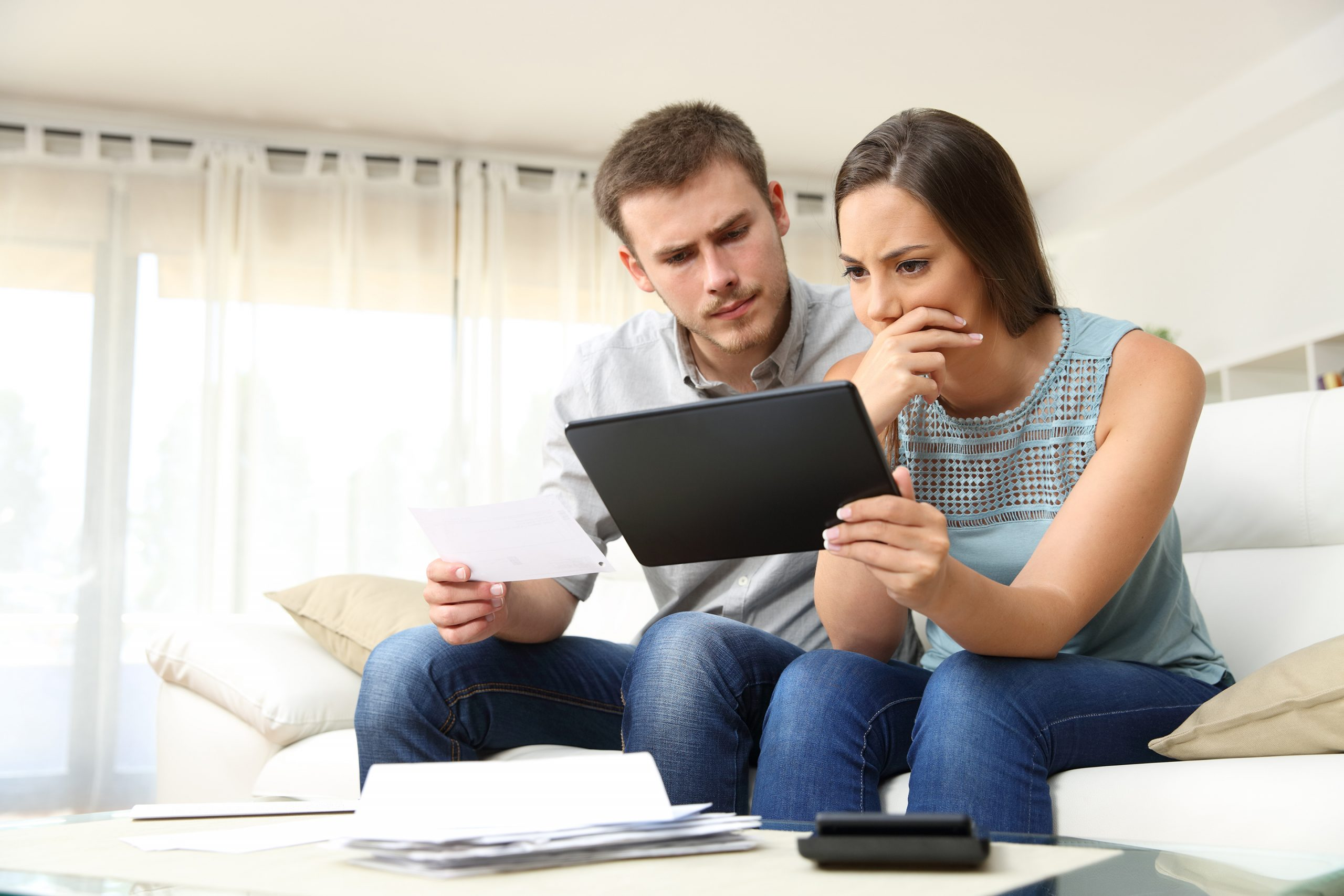 man and woman frowning over bills